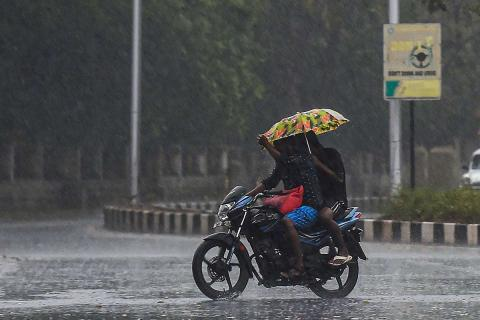 Two people ride on a motorcycle on the road in the rain while holding an umbrella