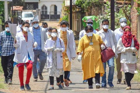 A group of doctors with masks and coats walking on the road