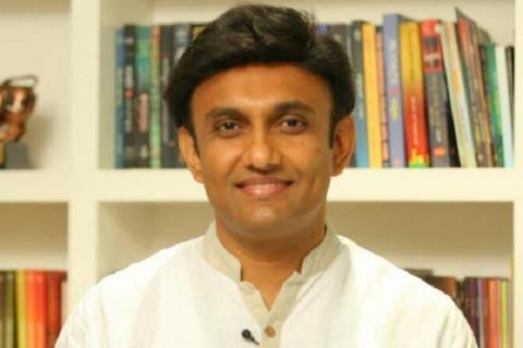 Health Minister Dr K Sudhakar standing in front of bookshelf