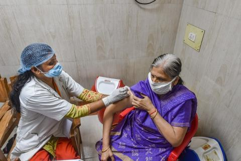 Elderly woman on the right gets the COVID-19 vaccination shot from a haelthcare worker on the right