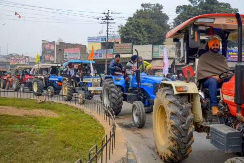 Farmers protesting in Delhi holding a small tractor rally