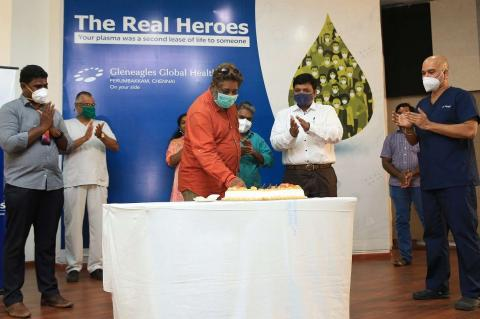 People at an event in Chennai wearing a mask and cutting a cake