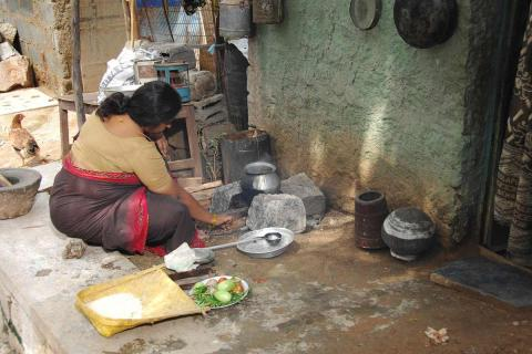 A domestic help or maid washing utensils
