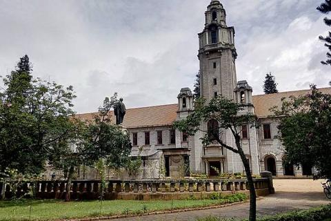 IISc campus against a grey sky with a green lawn and trees