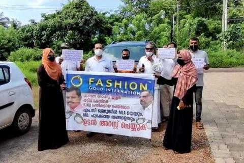 Men and women holding a banner demanding arrest of gold jewellers