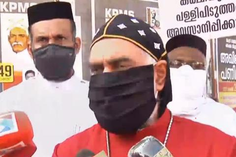 Joseph Mar Gregorious of Kerala Jacobite church in red cassock, wearing black mask.