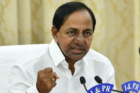 CM KCR, dressed in white, with his fist held tight and angrily looking at the camera