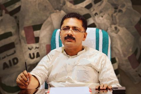 KT Jaleel is seen sitting at his desk. He looks serious in this image. He is holding a pen with a file on his desk. A faded image of the bags with UAE AID and flag printed on them are seen against the background of this posterised image.