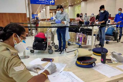 Passengers at Kochi international airport standing in queue. A security personnel is seen writing something sitting on her desk