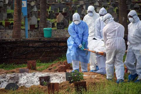 A corpse of a person, who succumbed to coronavirus, is being lowered into a grave by a few medical attenders in hazmat suit