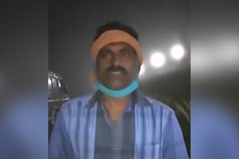 A man stands wearing a blue shirt with a piece of cloth bandaged around his head and his blue mask under his chin. It is night and there are lights in the background