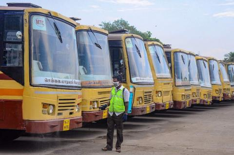 TNSTC buses in line and an employee cleaning it.