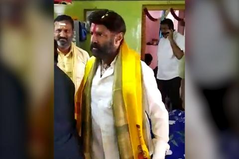 Actor politician Balakrishna wearing a white shirt and yellow scarf raising his hand to slap a man