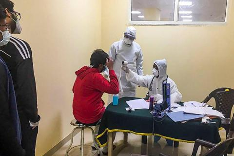 A man taking treatment at a clinic where doctors wear protective gear against coronavirus