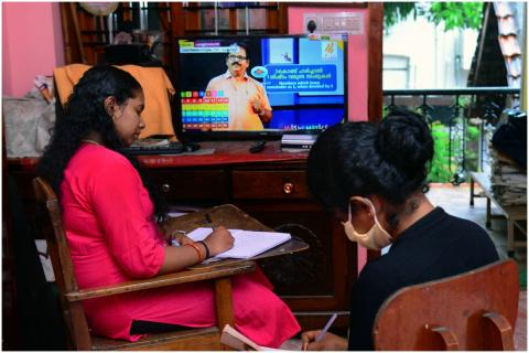Girl noting down lessons in book while attending virtual classes at her home through television. The girl is clad in a black top and is sitting near another woman in a pink salwar. There is a television in the room and VICTERS Channel is playing.
