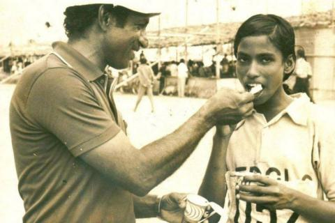 Black and white photo of Madhavan Nambiar feeding young PT Usha