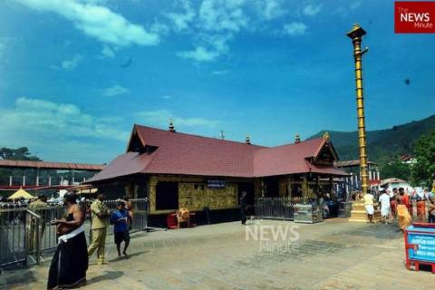 Sabarimala temple set against clear blue sky without the crowd, sparing a couple of people
