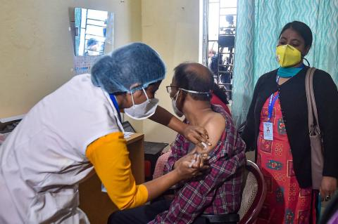 A female health worker administers COVID-19 vaccine to a male beneficiary as another woman looks on