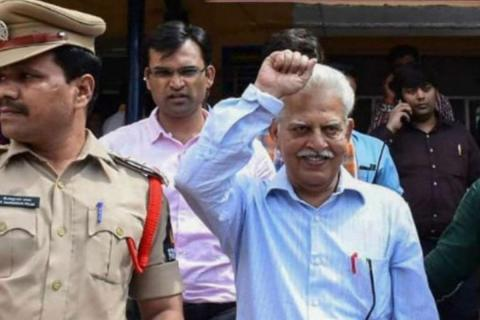 Poet Varavara Rao raising his fist towards the cameras with a smile as he is escorted by police