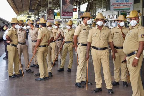Group of policemen stand around in arailway station while a train leaves the station. They are all wearing khaki, holding lathis, and wearing white face masks