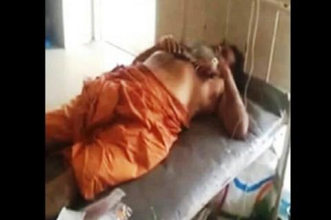 Godman lying down in a hospital bed