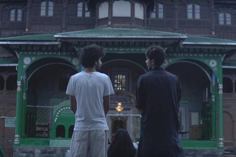 A still from the Kashmiri short film Jhelum, showing two young men looking at each other in front of a mosque.