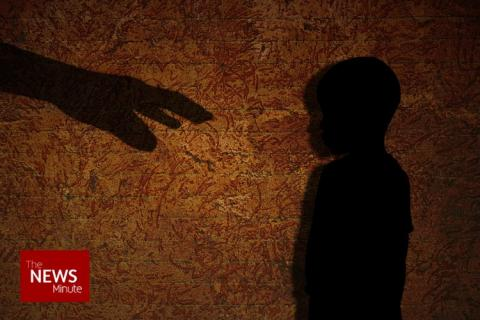 A hand reaching to a boy who is standing in shadow used as sexual Abuse of boy representative image.