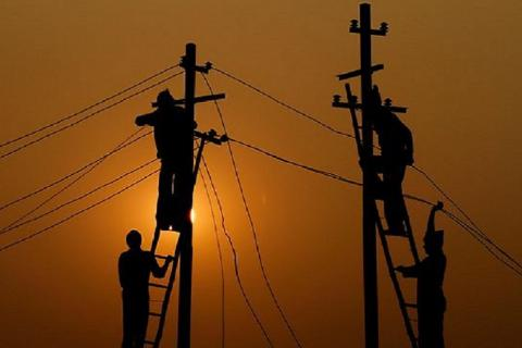 Silhouettes of men fixing wires on two electricity posts