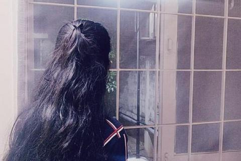 A picture of a woman from behind. She has long hair and is looking outside a window