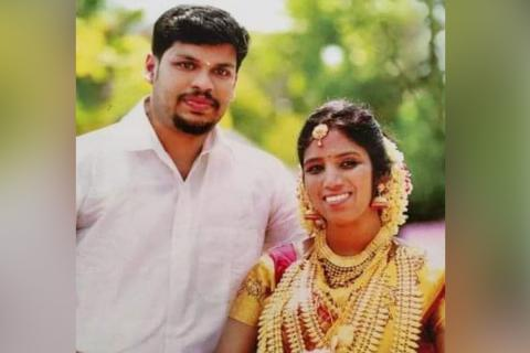 Wedding photo of Uthra and Sooraj. Uthra is seen in a red sari decked up with gold jewellery, while Sooraj, who is accused of killed Uthra, is seen in a white shirt. Both are smiling in the picture.
