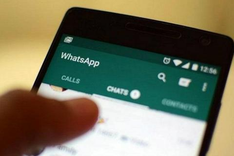 A person holding a phone with WhatsApp open, close up on the chats tab