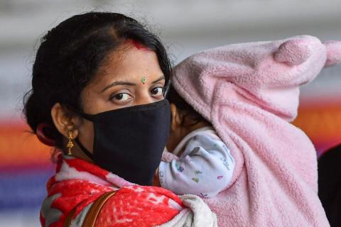 Mother wearing mask carrying a baby