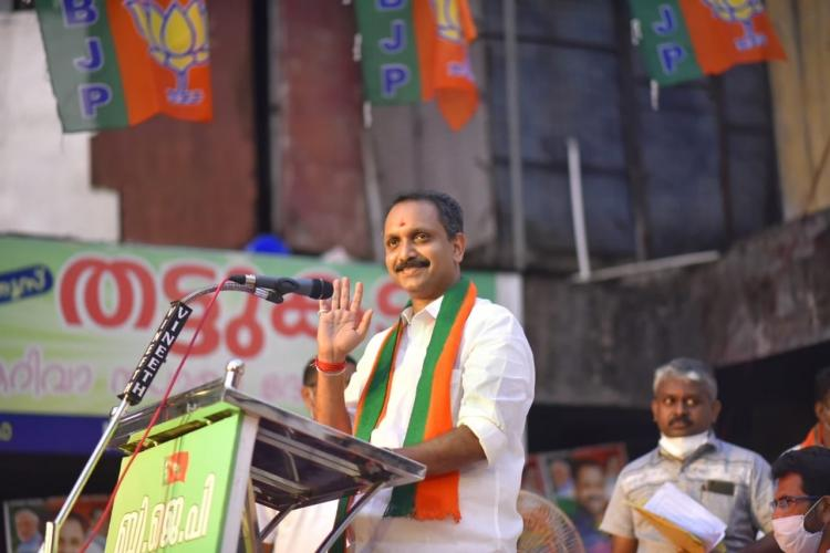 Kerala BJP chief K Surendran addressing a rally He is smiling in the picture and is wearing the BJP shawl around his neck