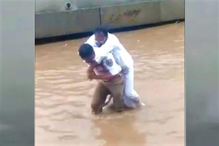 Watch Traffic cop rescues man carries him across waterlogged road in Hyderabad