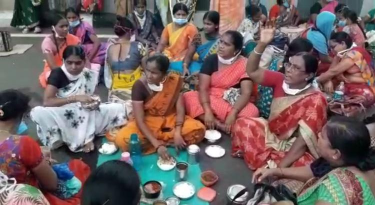 Sanitation workers of Gandhi sat on the road and are eating from thier lunch boxes as a mark of protest