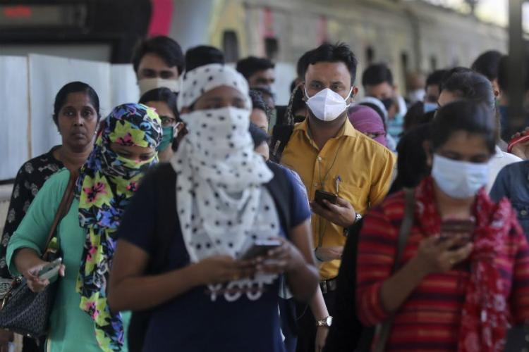 A group of people walking forwards and most of them were seen wearing masks