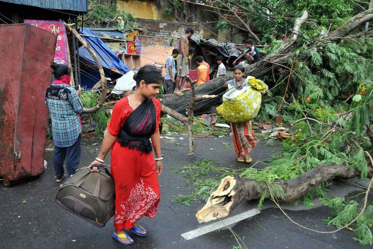 People retrieve belongings from their houses damaged in the aftermath of Cyclone Amphan at a slum in Kolkata