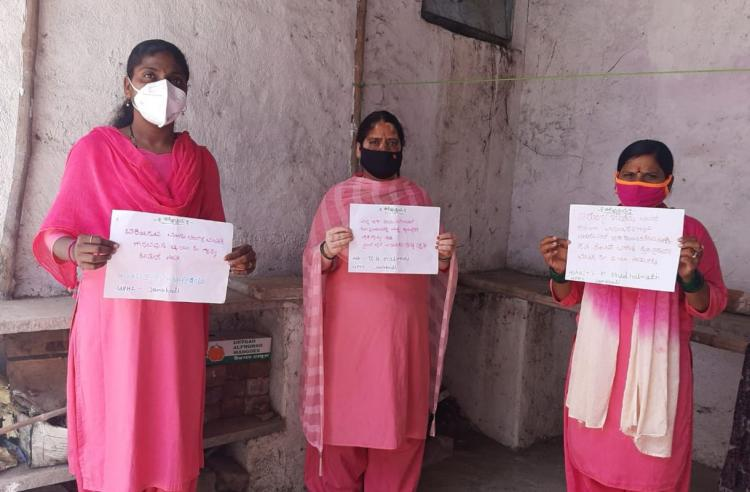 Three AASHA workers holding a poster with a list of their demands