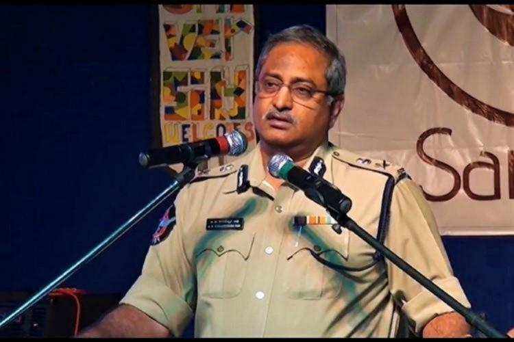 Suspended Andhra IPS officer AB Venkateswara Rao in police uniform speaking into two mics on a stage at an event