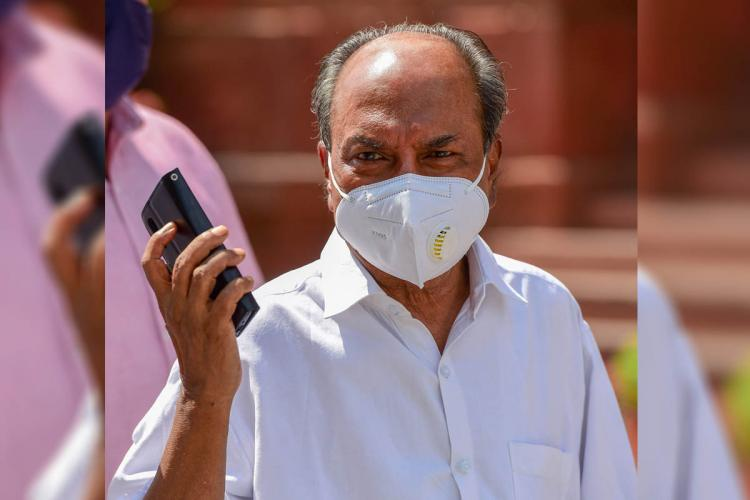 AK Antony standing He wears a face mask and is holding a phone in his hand