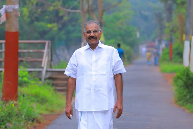 Saseendran wearing his white shirt and mundu walks on a road filled with greenery on either side