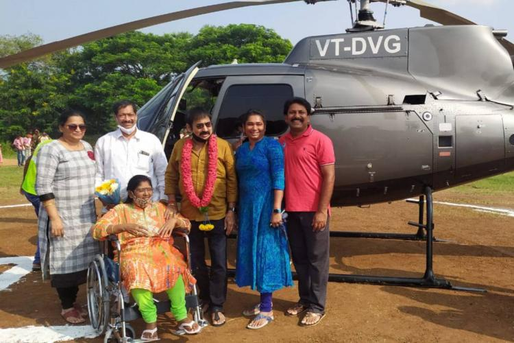 A group of people standing in front of a helicopter