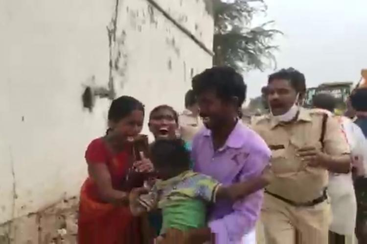Two women and a man carrying an injured child and crying as a police officer approaches them