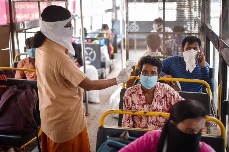 An APSRTC worker conducts thermal screening of a passenger at Pandit Nehru Bus Station in Vijayawada