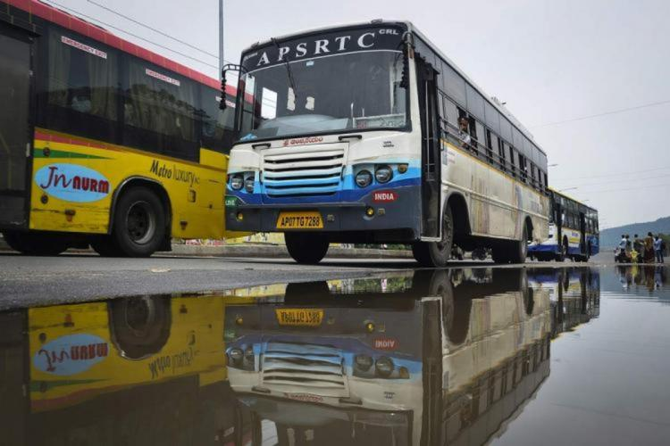 An APSRTC bus parked in a depot with water stagnated in front of it