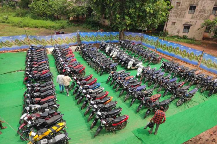 Top angle view of more than 100 stolen motor bikes arranged in an orderly manner in rows in East Godavari district on a green carpet