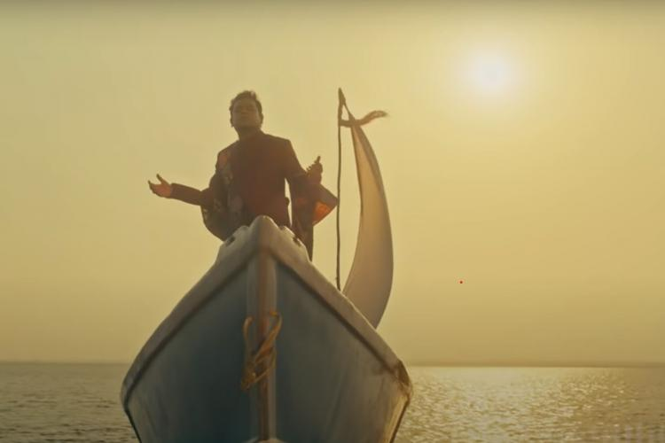 AR Rahman standing on a boat in the ocean with the sun in the background in teaser of new track Moopilla Thamizhe Thaaye