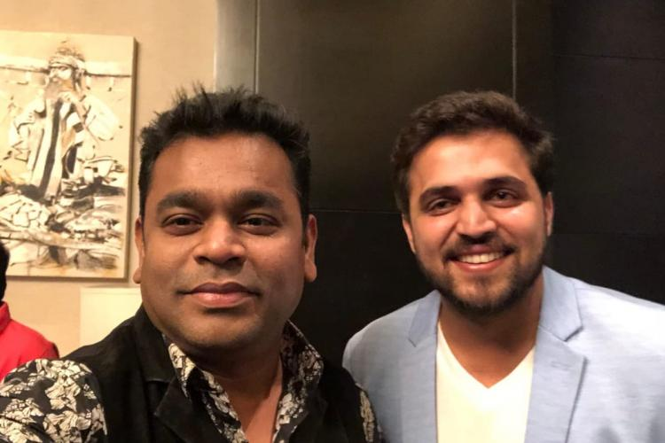 Singer Nakul Abhayankar in a blue suit with music composer AR Rahman who is wearing a black shirt