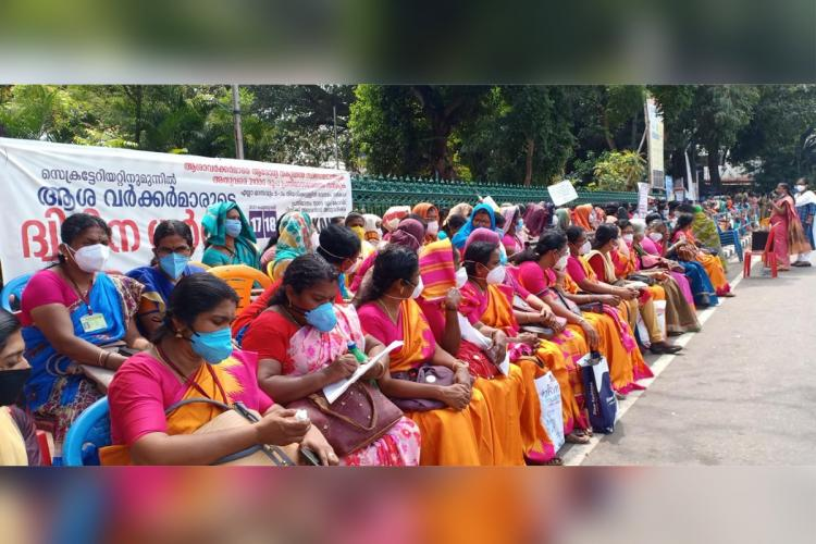 A number of ASHA workers are sitting in two rows in front of the Secretariat for a protest