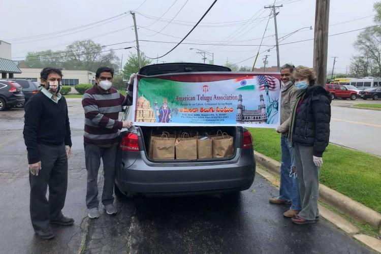 Four members of the American Telugu Association distribute essentials amid the coronavirus pandemic They are standing next to a car with its boot open showing relief material and a banner of the organisation